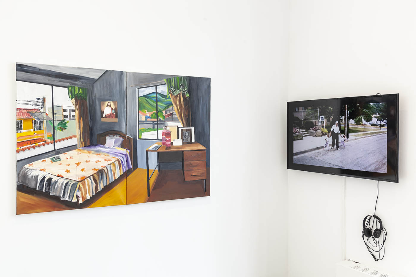 Exhibition view: Painting of bedroom, and a video monitor of a man crossing a suburban street.