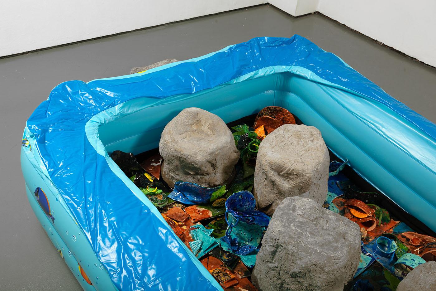 Detail of sculpture: ceramic tiles inside of a plastic pool.