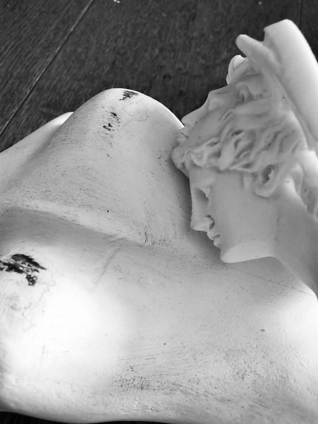 Black and white photo of classical sculpture head resting on torso of female sculpture.