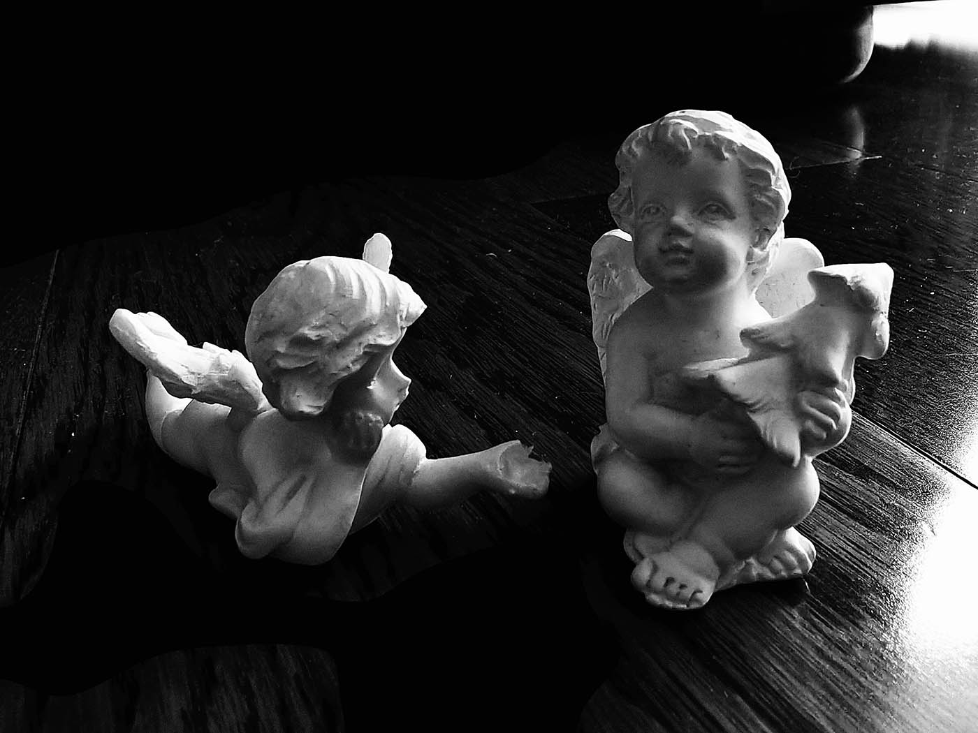 Black and white photo of two classical cherub sculptures.