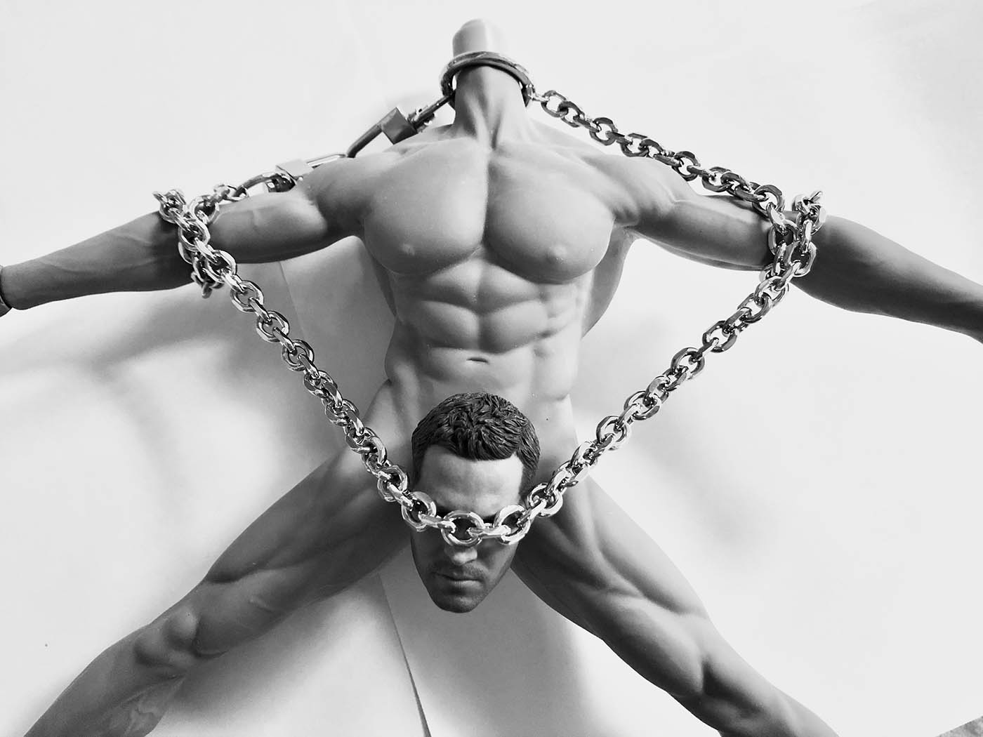 Black and white photo of nude male scultpure holding large chain.
