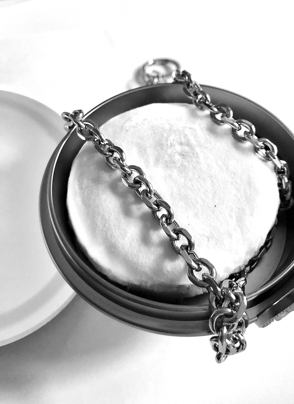 Black and white photo of makeup case depicted as ball and chain.